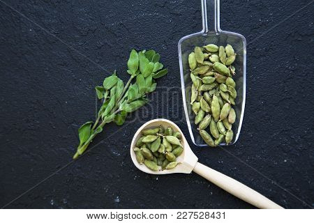 Dry Beans In A Glass And Wooden Spoon And Glass Jar , Fresh Herbs On A Black Stone Background With C