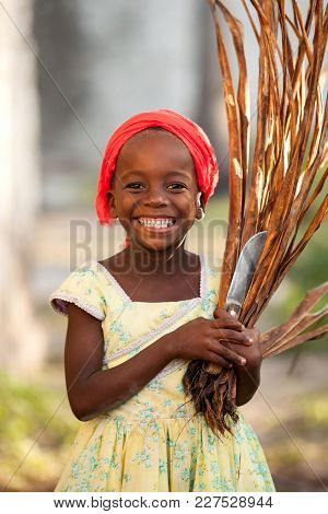 Stone Town, Zanzibar - January 20, 2015: Girl Smiling With Grass Cuttings And A Knife In Hand