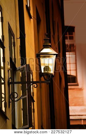 Old Metal Streetlamp With Economical Modern Bulb On The Yellow Wall