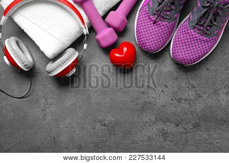 Gym stuff and red heart on grey background. Cardio training concept