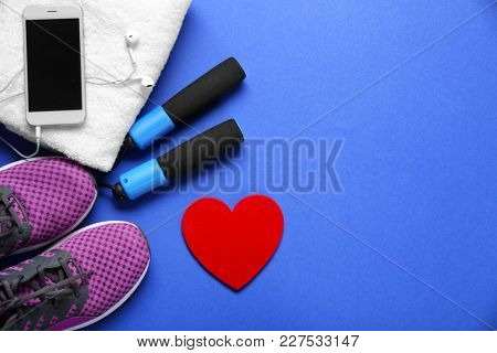 Gym stuff, phone and red heart on color background. Cardio training concept