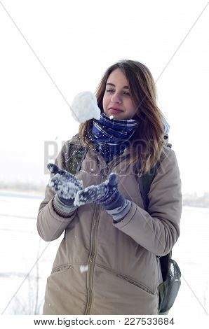 A Young And Joyful Caucasian Girl In A Brown Coat Holds A Snowball In The Background Of A Horizon Li
