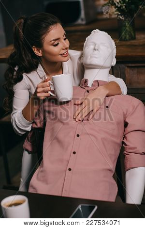 Young Woman With Cup Of Coffee Hugging Mannequin At Home, Perfect Relationship Dream Concept