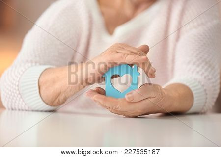 Senior woman with house figure at table. Home care concept