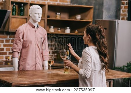 Woman With Glass Of Wine And Manikin In Casual Clothing In Kitchen At Home, Unrequited Love Concept