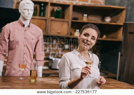 Selective Focus Of Woman With Glass Of Wine And Manikin In Casual Clothing In Kitchen At Home, Unreq