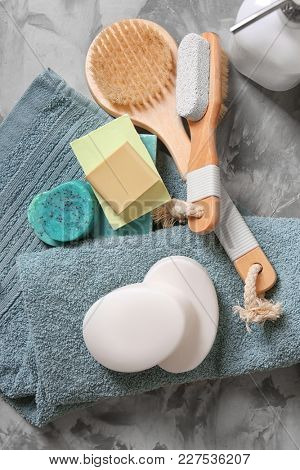 Soft towel, different soap bars and bath accessories on table