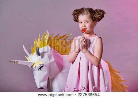 Portrait Fashion Kid. Child Fashion Concept. Romantic Lady Girl In Pink Dress Eats A Little Lollipop