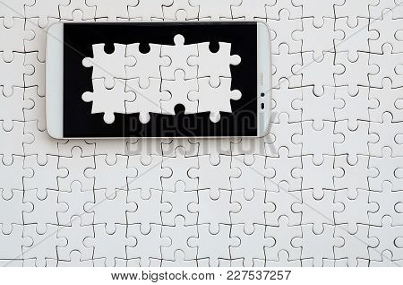A Modern Big Smartphone With Several Puzzle Elements On The Touch Screen Lies On A White Jigsaw Puzz