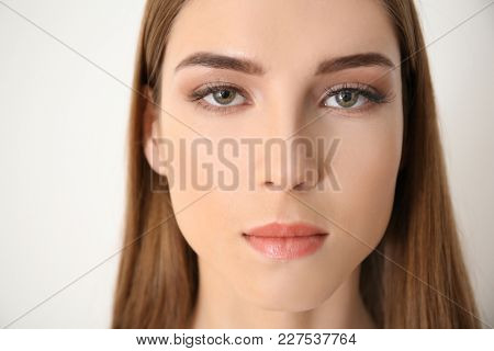 Young woman with eyelash loss problem on white background