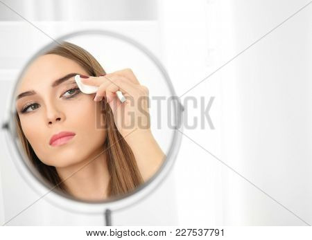 Young woman removing makeup in front of mirror indoors. Eyelash loss problem