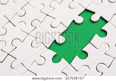 Close-up Texture Of A White Jigsaw Puzzle In Assembled State With Missing Elements Forming A Green P