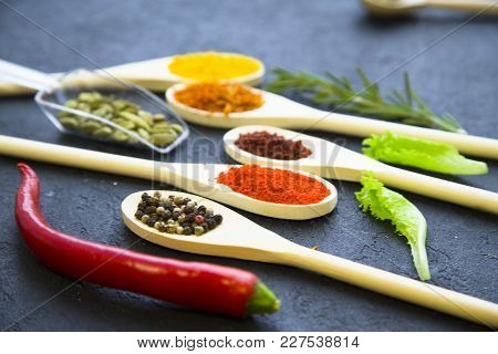 Dry Spices And Herbs In Glass And Wooden Spoons, Fresh Herbs And Chili Pepper, Black Stone Backgroun