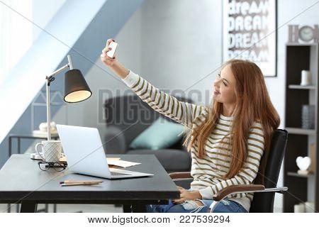 Beautiful smiling woman taking selfie at home