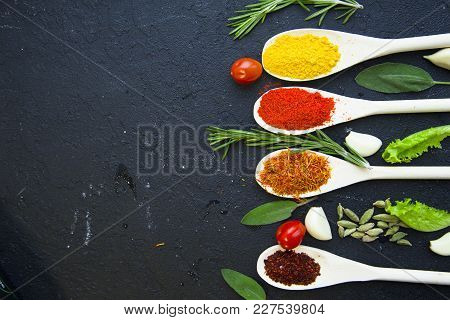 Dry Spices And Herbs In Wooden Spoons, Fresh Herbs, Cherry Tomatoes And Garlic, Black Stone Backgrou
