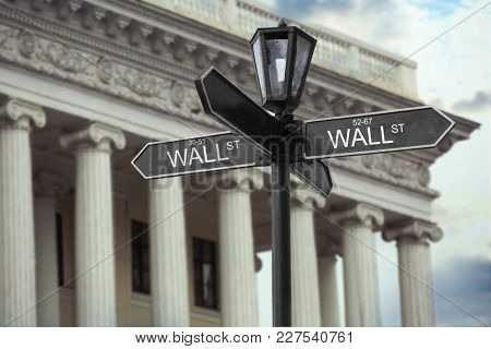 Wall Street signboard and stock exchange building on background