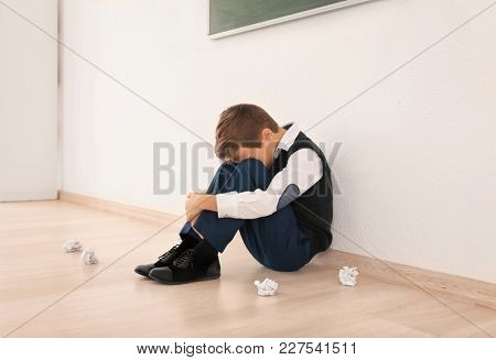 Upset little boy sitting on floor indoors. Bullying in school