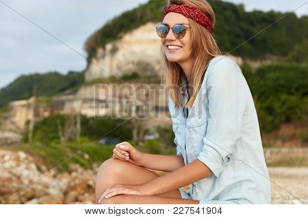 Beautiful Young Female Dressed In Casual Shirt, Red Bandage On Head And Sunglasses, Admires Wonderfu