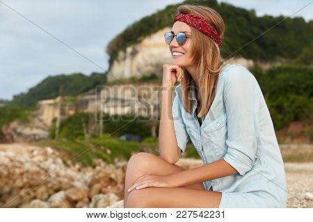 Happy Young Female Tourist Spends Summer Tour In Mountains, Dressed In Comfotable Clothes, Wears Shi