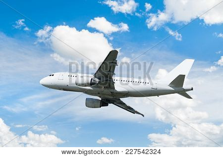 Airplane in the sky. Commercial white airplane flying in the blue sunny sky. Travel background with flying airplane, air travel concept. White commercial airplane with blank livery, airplane in the flight