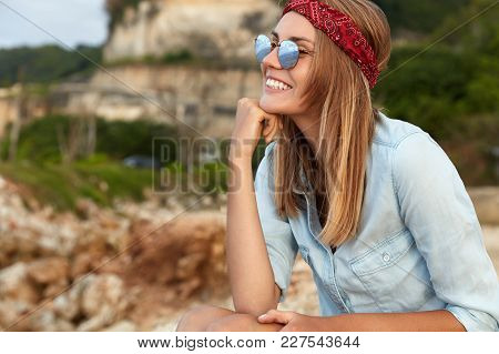 View Of Happy Stylish Young Woman In Fashionable Clothes, Wears Shades, Sits Against Mountain Backgr