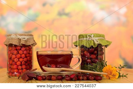 Banks With Dry Rosehip Berries And Mountain Ash, Cup Of Vitamin Tea And Saucer, On Beige Wooden Tabl