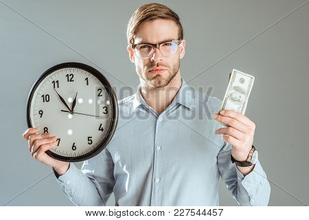 Young Thoughtful Businessman Showing Money And Clock Isolated On Grey