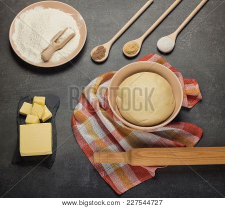 Finished Dough In A Bowl On A Towel, Flour And Butter On Gray Surface