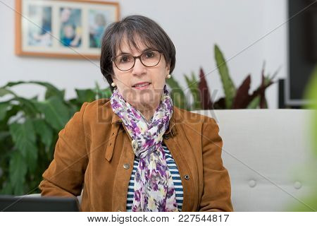 Charming Mature Woman With A  Brown Jacket And Glasses