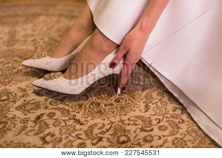 The Bride Touches Her Beige Wedding Shoes. Wedding Day. Wedding Dress