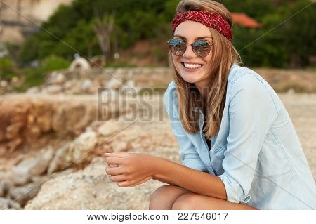Positive Female With Pleasant Appearance, Dressed Casually, Looks Happily Into Distance While Sits O