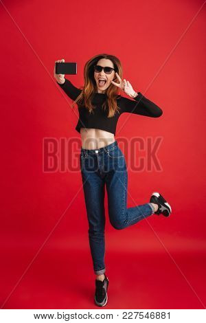 Picture of young cute lady isolated over red background make selfie by mobile phone. Looking aside showing peace gesture.