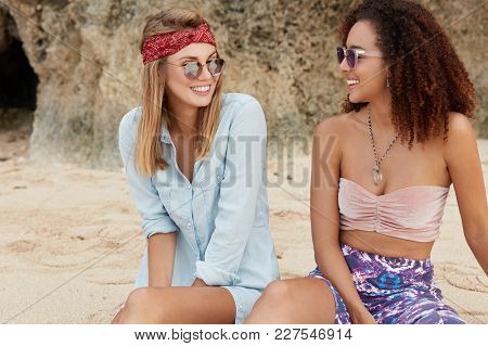 Outddor Shot Of Females Lesbians Have Fun Together On Rock, Enjoy Good Recreation, Look At Each Othe