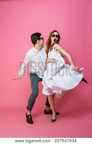 Full-length photo of crazy artistic girl and guy in classy stylish clothing dancing and partying isolated over pink background