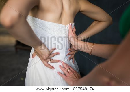 Bridesmaid Helps Fasten A Wedding Dress The Bride Before The Ceremony. Wedding. Bridesmaid Preparing