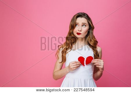 Photo of young sad woman standing isolated over pink background holding broken heart. Looking aside.