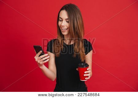 Photo of lovely woman with long brown hair communicating via smartphone while holding takeaway coffee in hands isolated over red background