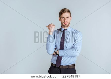 Young Unsatisfied Businessman Pointing Isolated On Grey