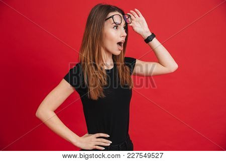 Closeup image of young woman 20s wearing black t-shirt taking off glasses and looking aside in surprise, isolated over red background
