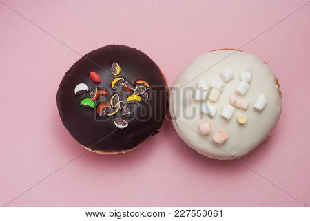 Top View Doughnuts With Chocolate And White Icing On Pastel Pink Background. Sweet Dessert Donuts