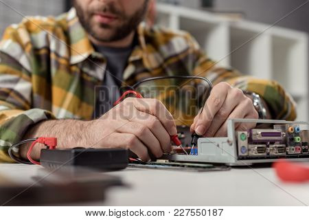 Cropped Image Of Man Using Multimeter While Fixing Broken Computer