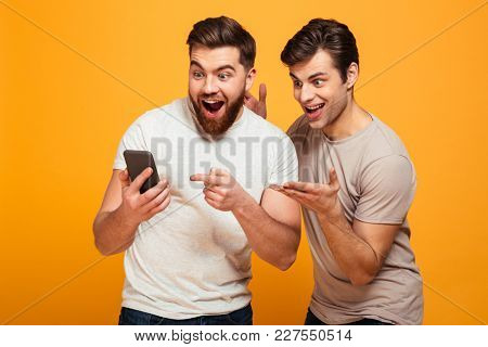 Portrait of a two cheerful young men looking at mobile phone isolated over yellow background