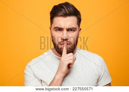 Portrait of a serious bearded man showing silence gesture isolated over yellow background