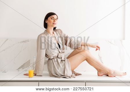 Portrait of sexual slim woman with short dark hair wearing robe posing in kitchen sitting on table in sunny morning and drinking orange juice