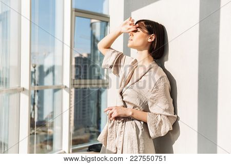 Young gentle woman with short dark hair in housecoat standing sunlit near window and covering face in sunny morning