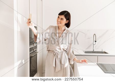 Single lovely woman with short dark hair wearing sexual robe posing in kitchen and taking selfie on cell phone