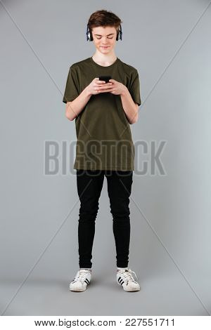Full length portrait of a happy male teenager wearing t-shirt listening to music with headphones while standing and using mobile phone isolated over gray background