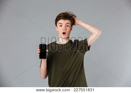Portrait of a shocked male teenager wearing t-shirt showing blank screen mobile phone and looking at camera isolated over gray background