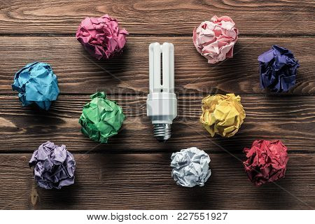 Set Of Multiple Colorful Crampled Paper Ball And Lightbulb Among Them, Placed On Wooden Table As Mea