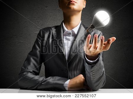Businessman In Suit Presenting Glowing Lightbulb In Hand As Symbol Of New Idea, Dark Wall On Backgro